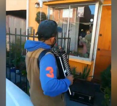 Joven toca acordeón para sus padres enfermos desde fuera de la casa